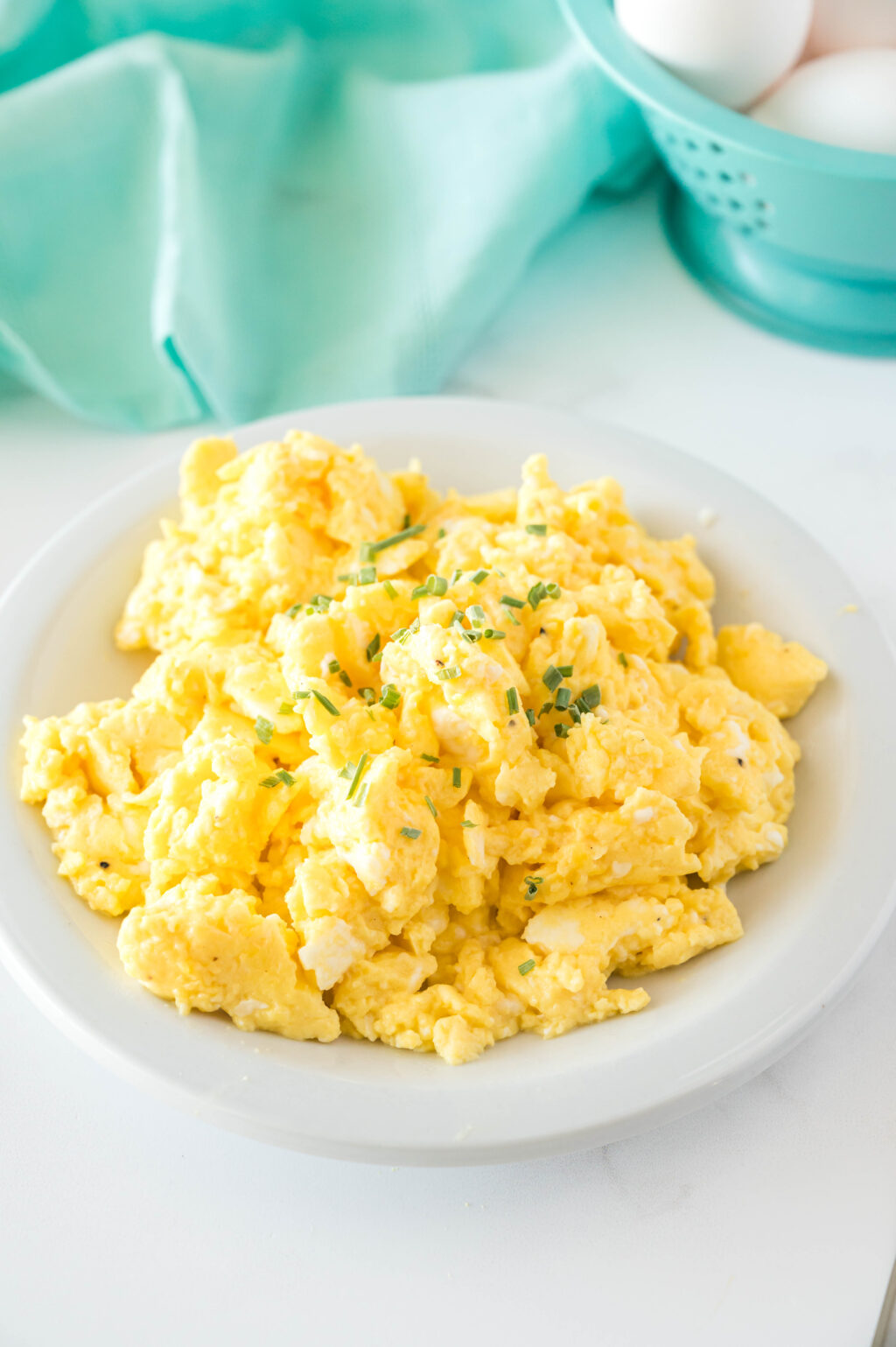 fluffy scrambled eggs on a white plate