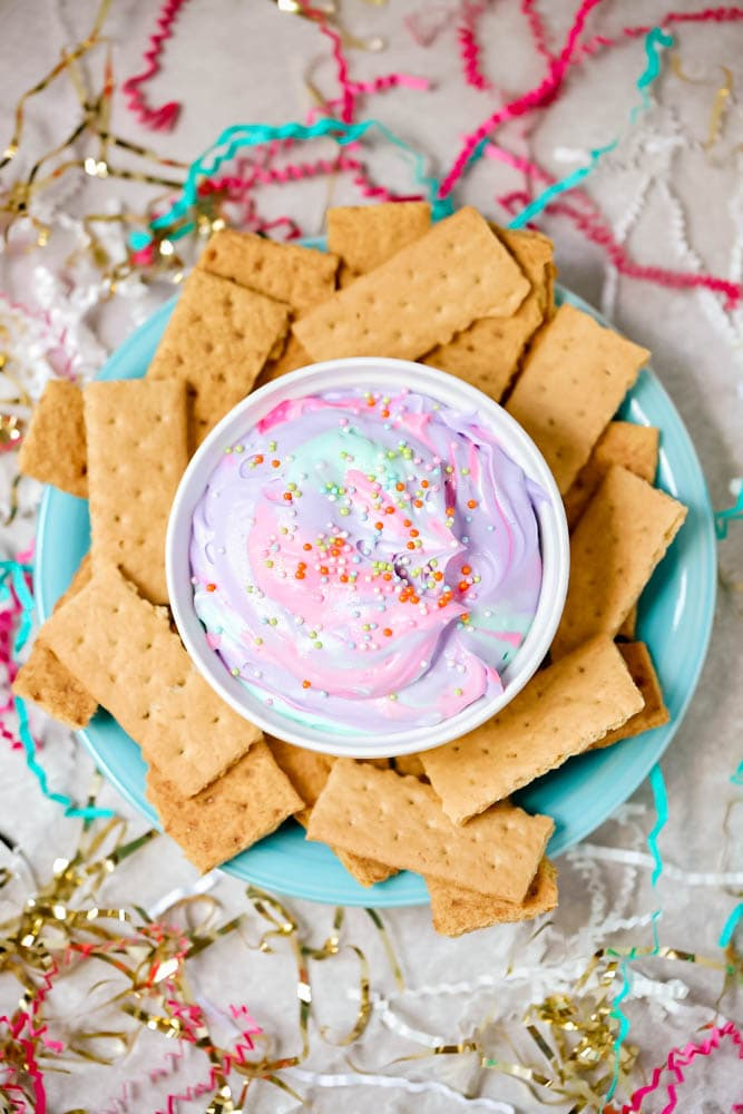 unicorn dip in a bowl surrounded by graham crackers
