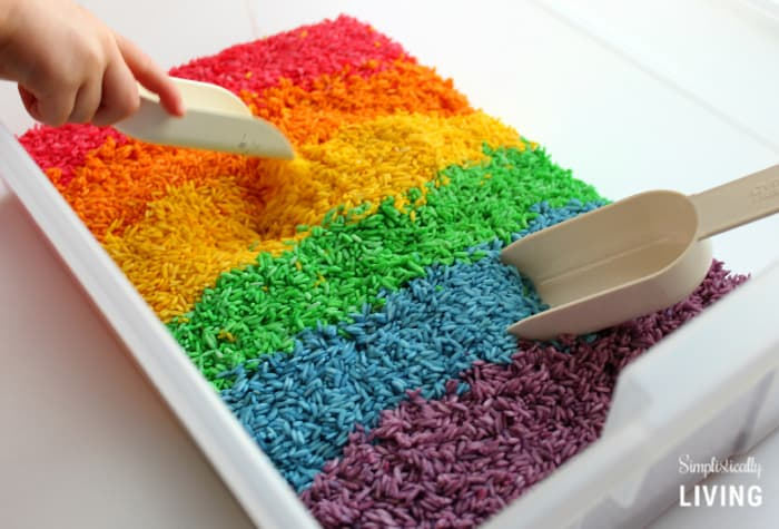 kid playing with rainbow rice