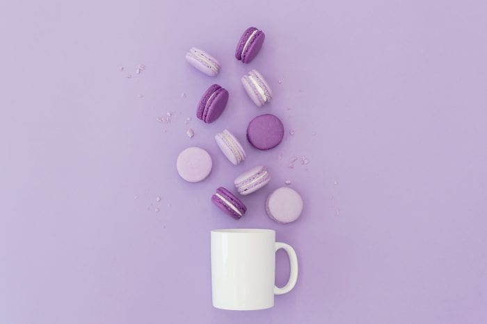 lavender macarons on purple background with coffee mug