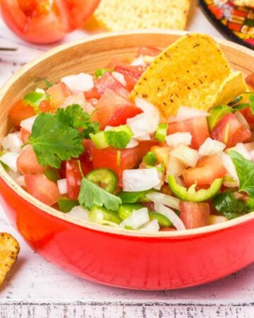 Bowl of fresh mexican Pico de Gallo salsa. Homemade salsa with crispy corn nachos chips.