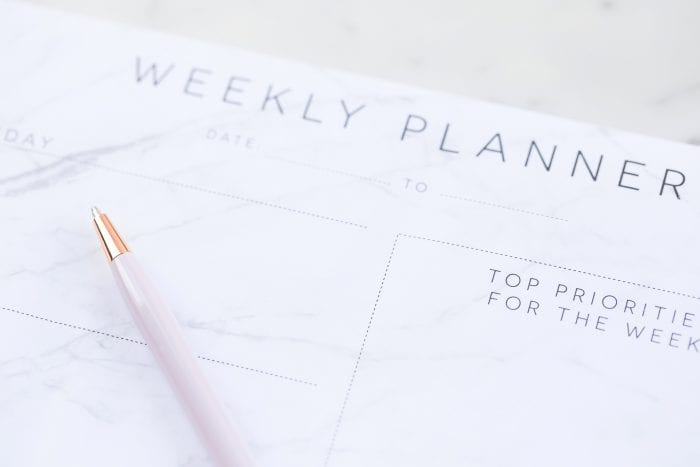 picture of a weekly planner with a pen sitting on top
