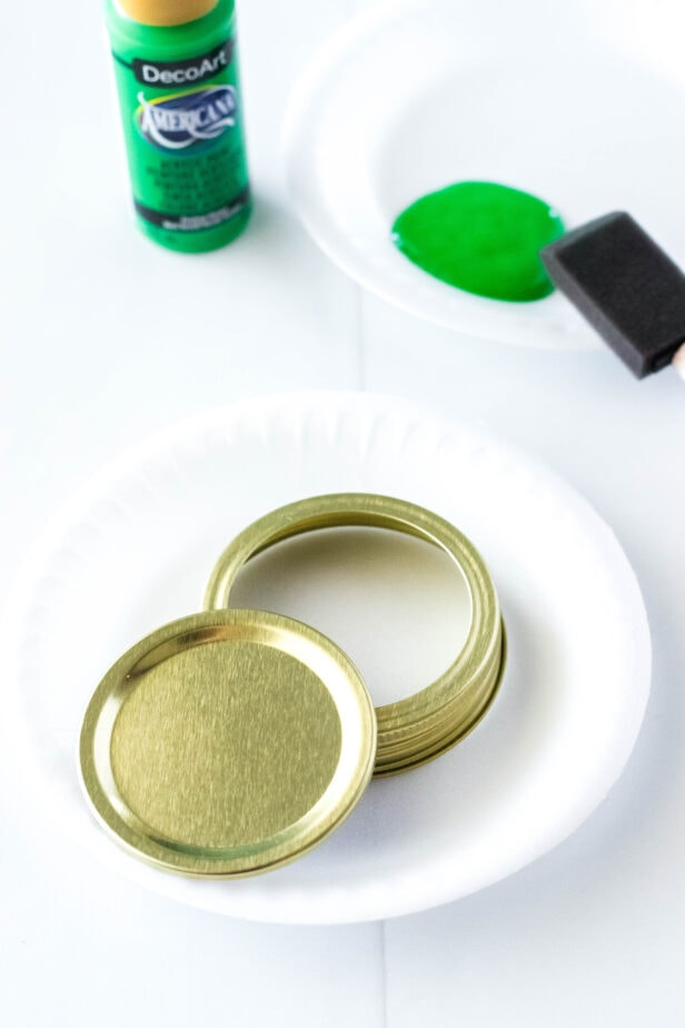 green paint on a paper plate with unpainted jar lids