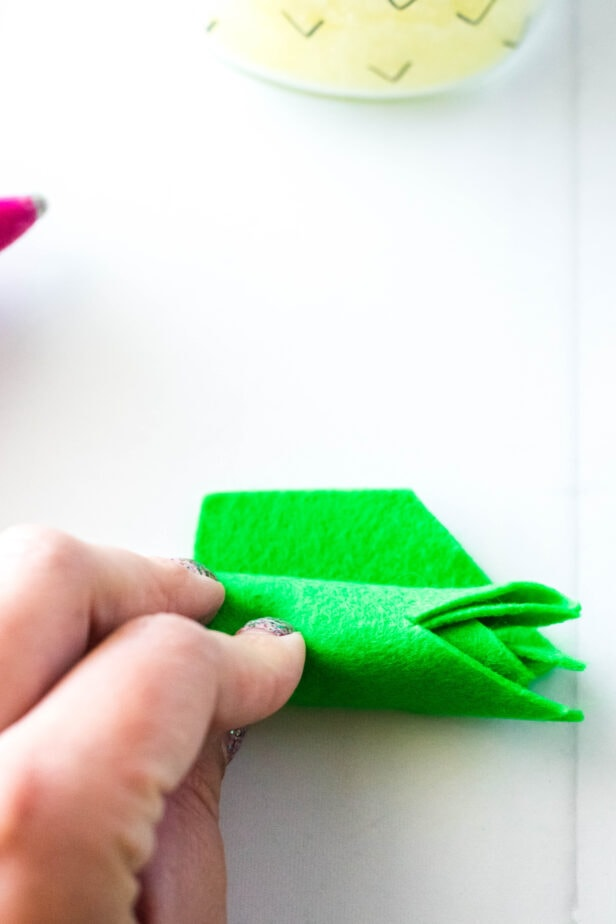 fingers holding green felt and rolling it