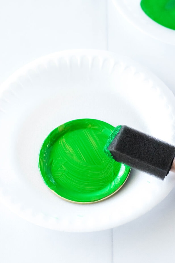 jar lids painted green on a paper plate