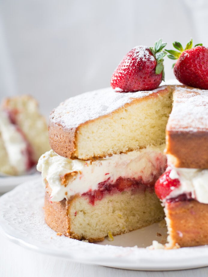 sponge cake cut open with frosting and berries