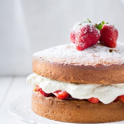 side shot of a sponge cake with strawberries and whipped cream on top