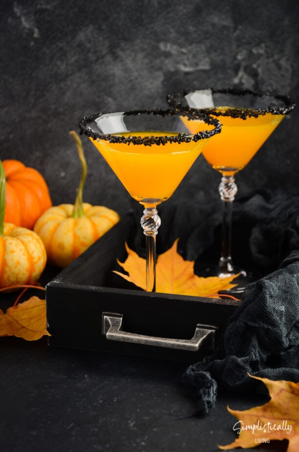 picture of orange cocktail with black sugar around the rim of the glass