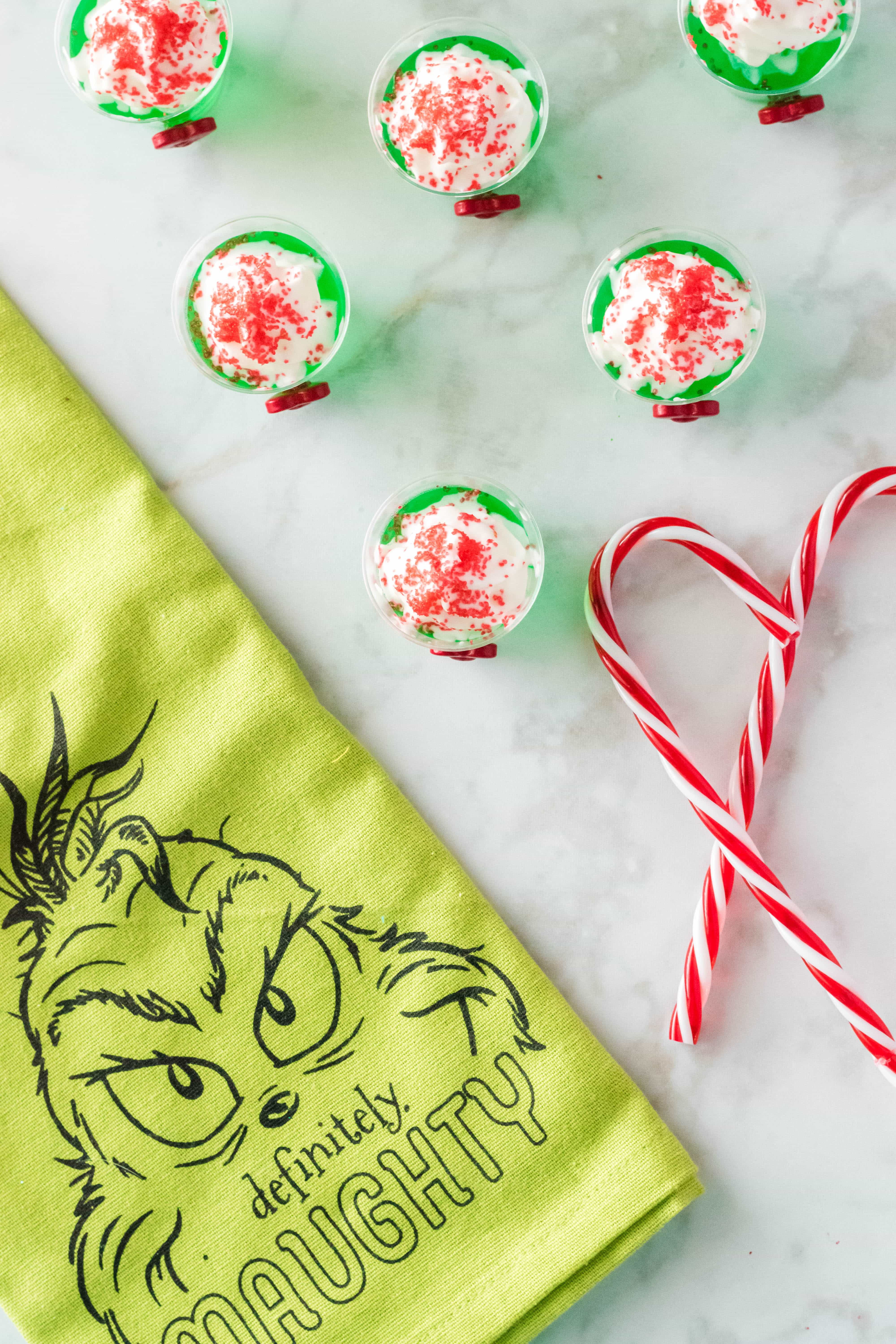 top view of grinch jello shots with a grinch themed towel