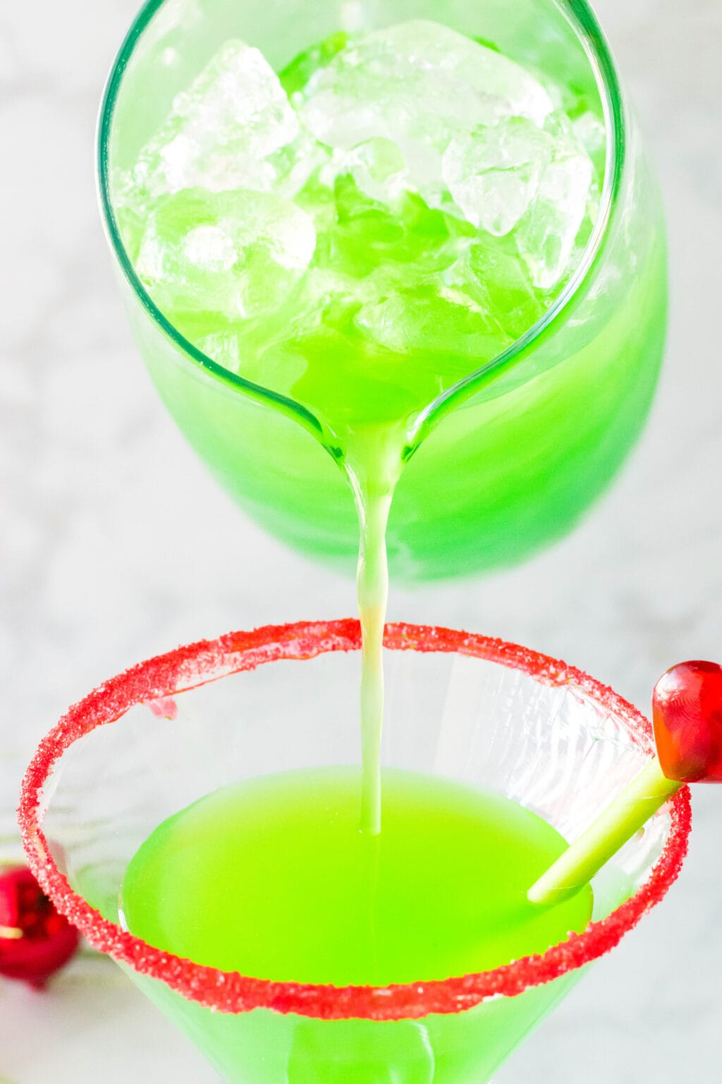 pouring grinch cocktail drink into glass