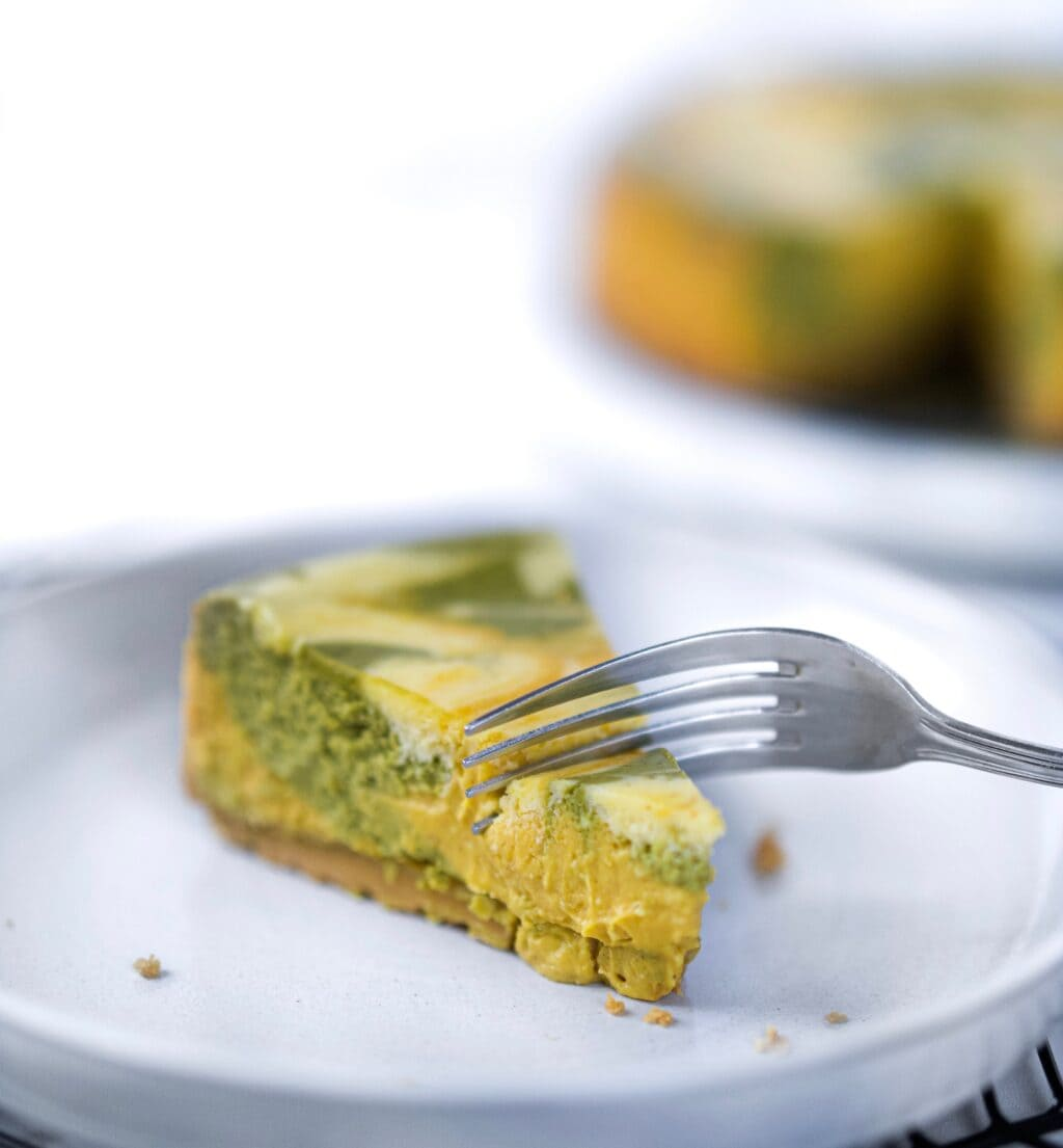 Fork cutting into piece of matcha pumpkin cheesecake