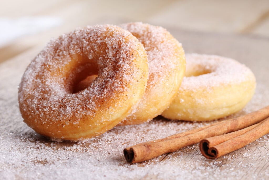 donuts on a table next to cinnamon sticks