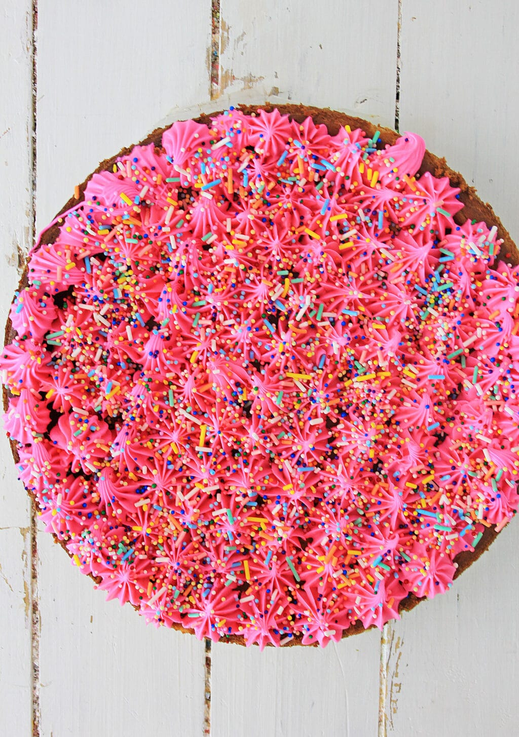 A top view of cheesecake with hot pink frosting and rainbow sprinkles