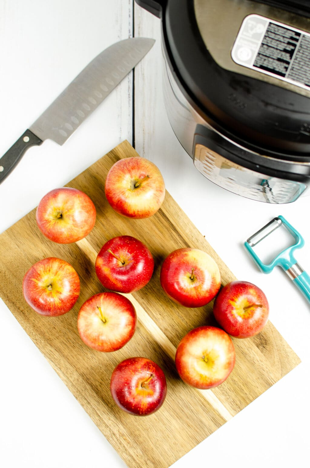 apples on a cutting board with an instant pot in the back