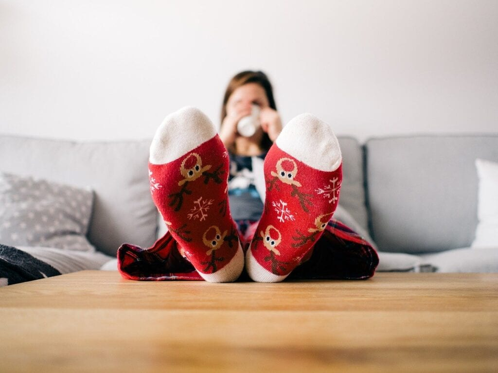 mom relaxing on couch wearing Christmas socks and drinking coffee
