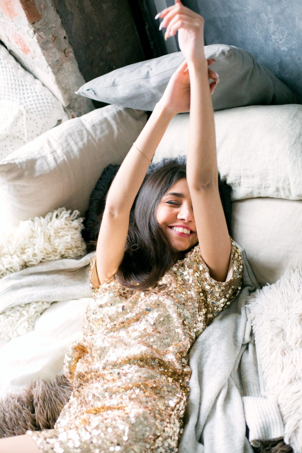 a woman laying on a bed smiling