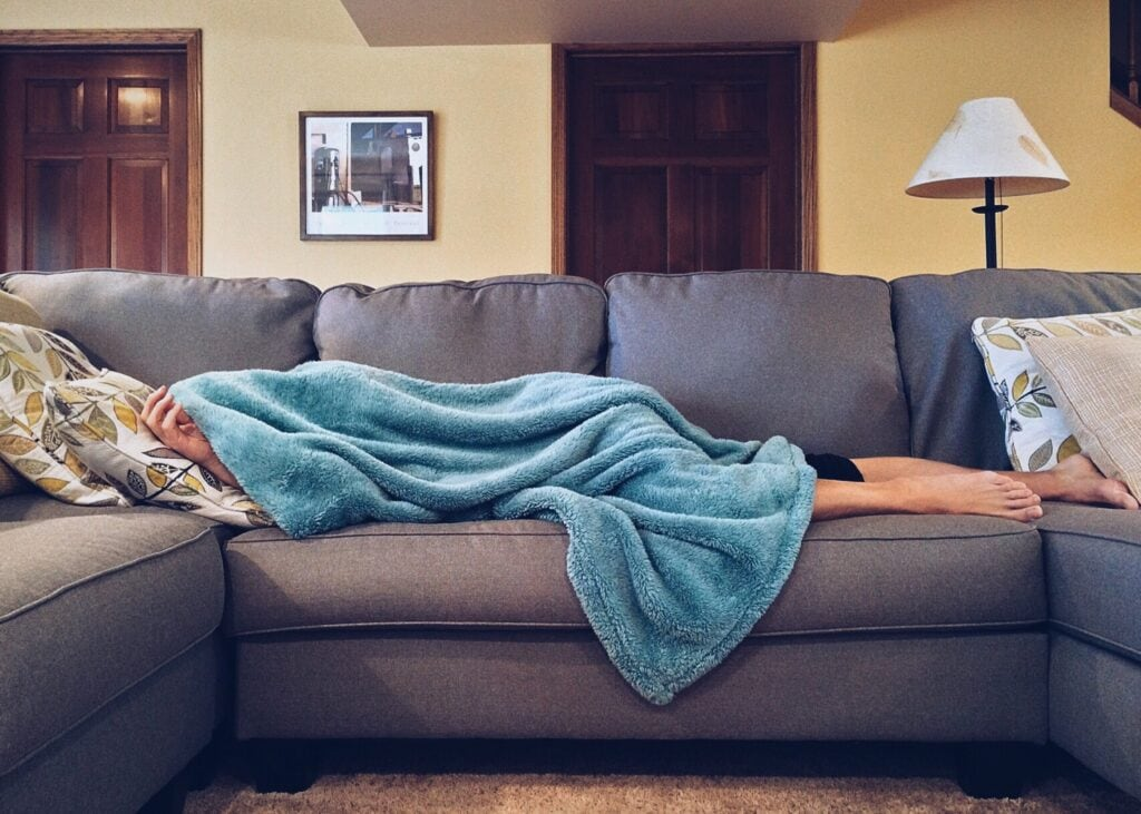 a person asleep on the couch with a blanket pulled over them