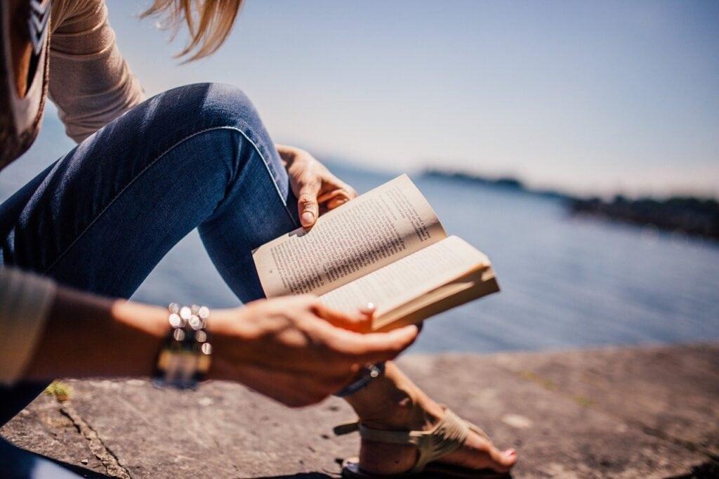 woman reading a book near a lake