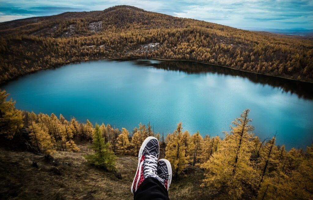 person relaxing on mountain overlooking a lake