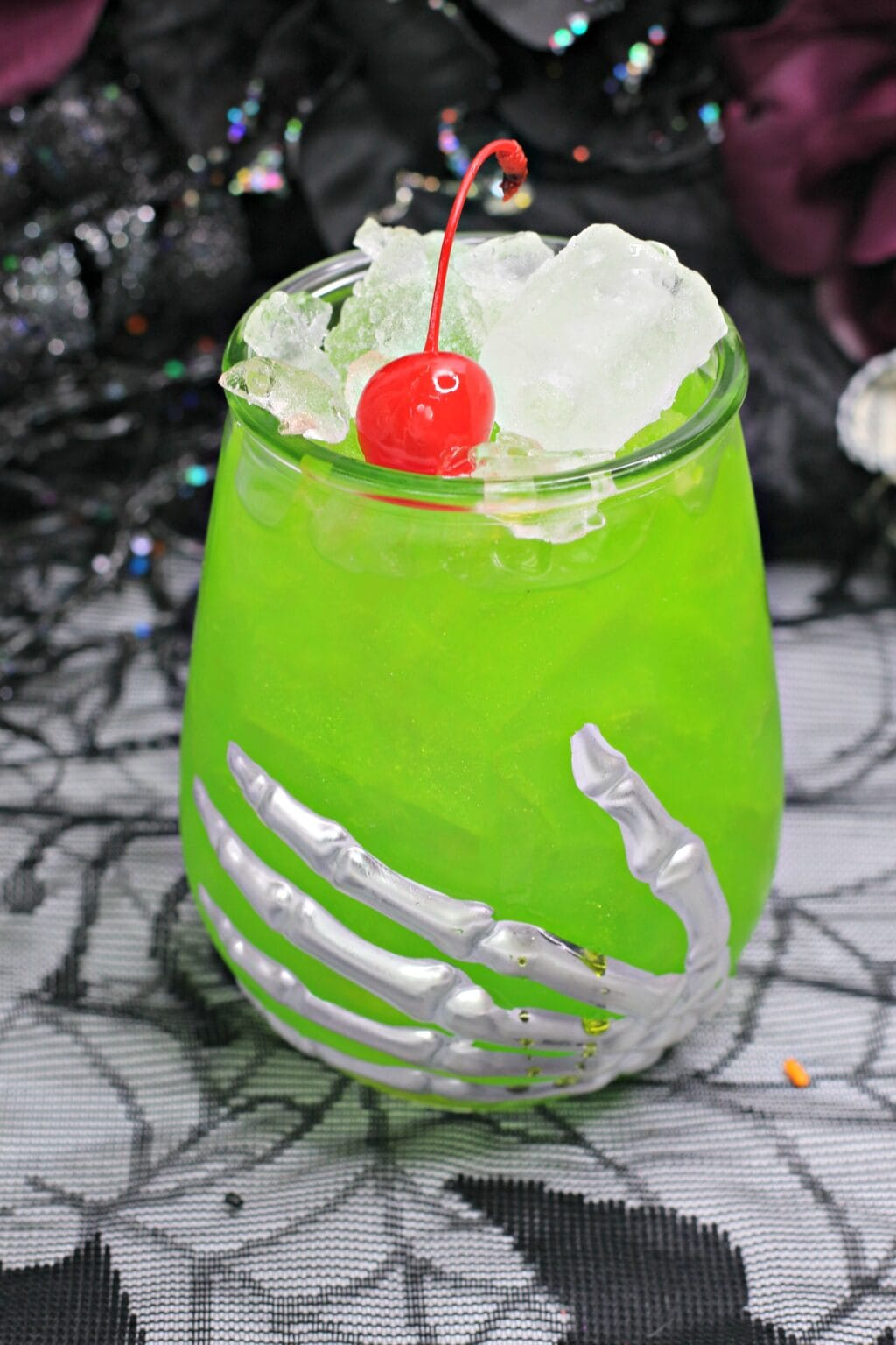 green Halloween cocktail in a skeleton cocktail glass with ice and a red cherry