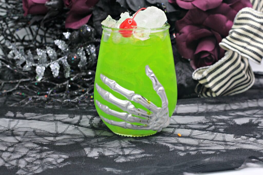 horizontal photo of green hocus pocus cocktail in a Halloween glass