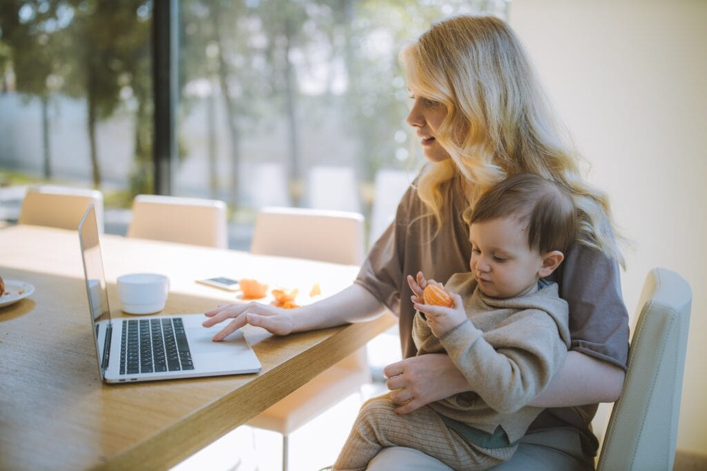 mom holding baby with laptop