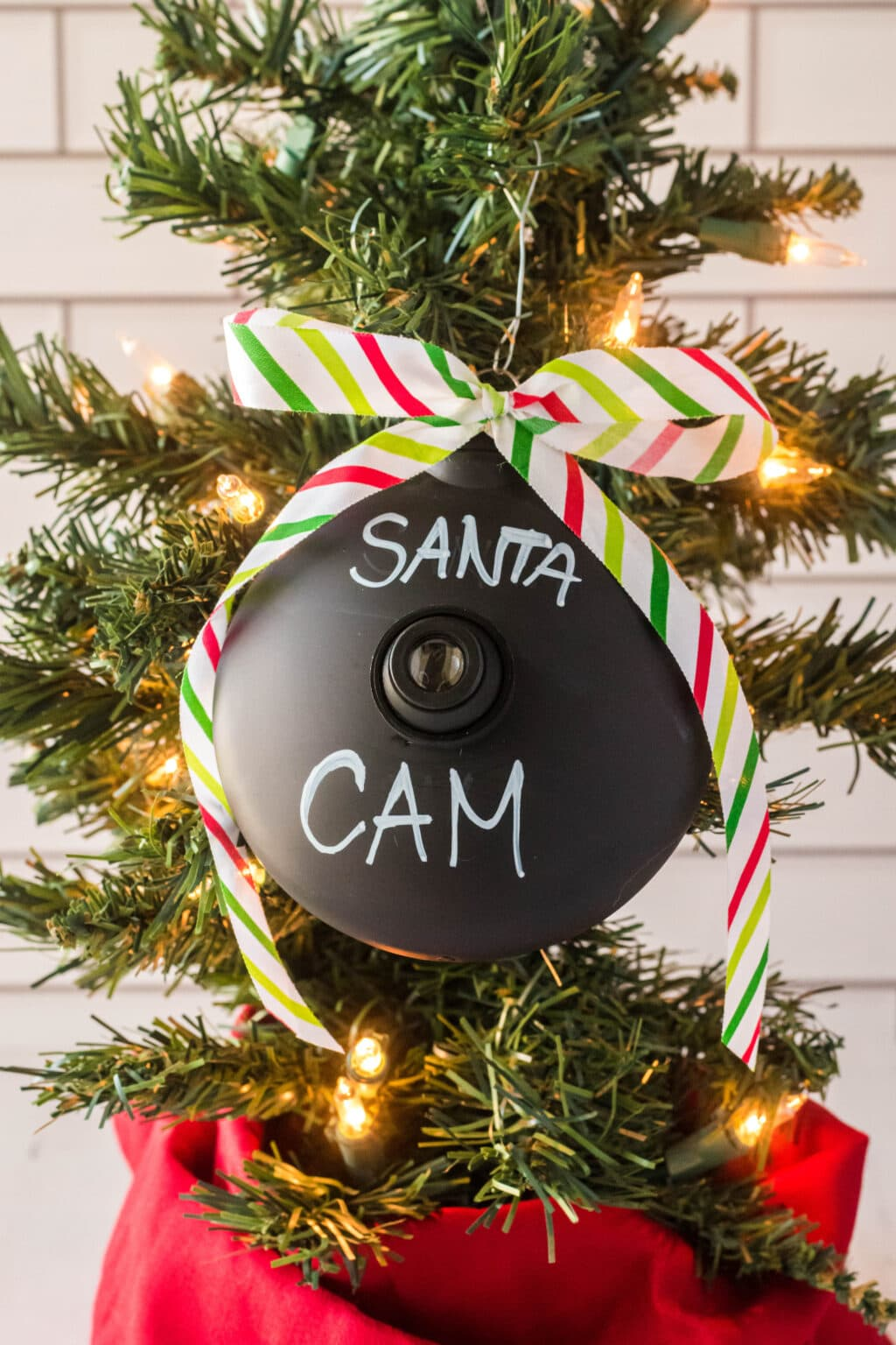 santa cam ornament hanging on a Christmas tree