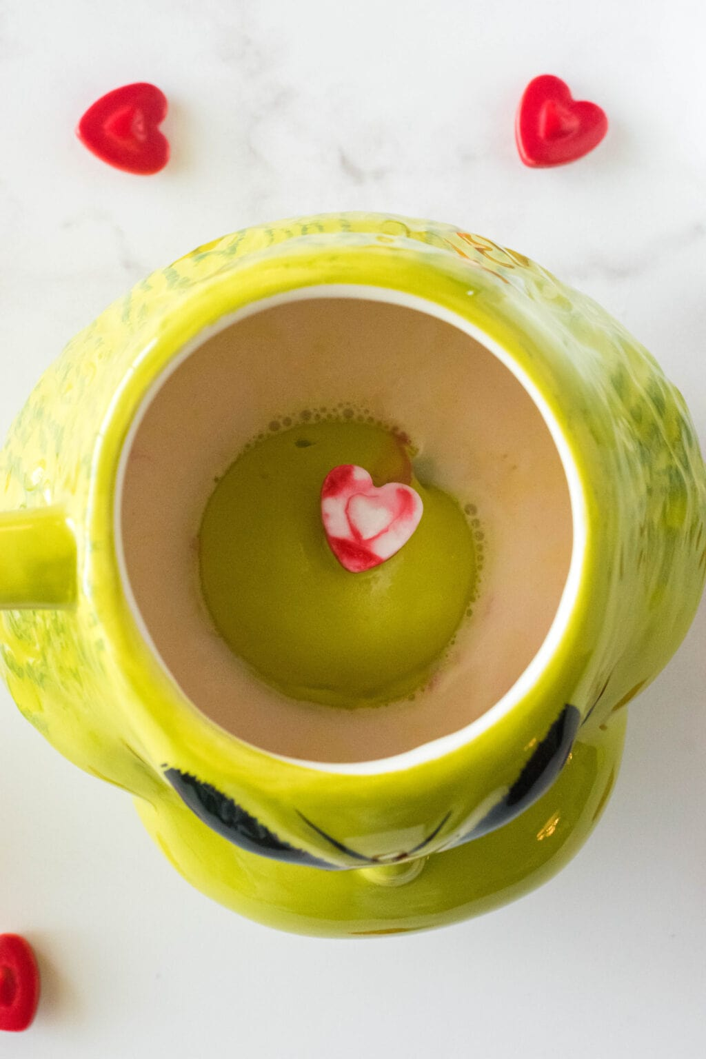 grinch hot cocoa bomb being melted into a grinch mug with hot milk