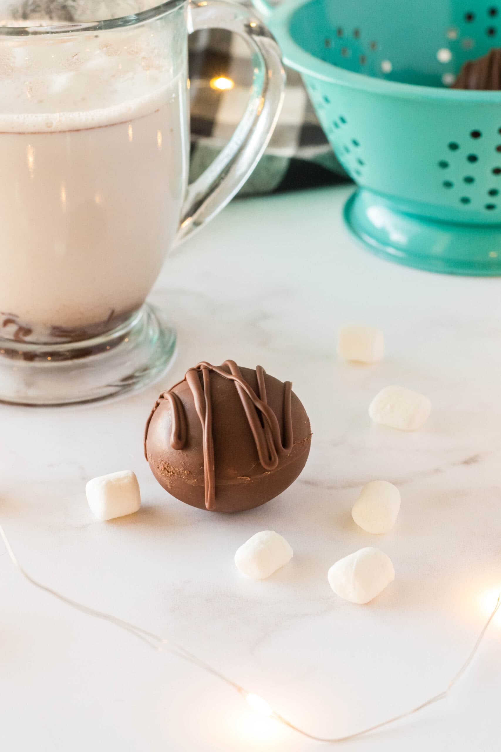 hot cocoa bombs on a table surrounded by mini marshmallows