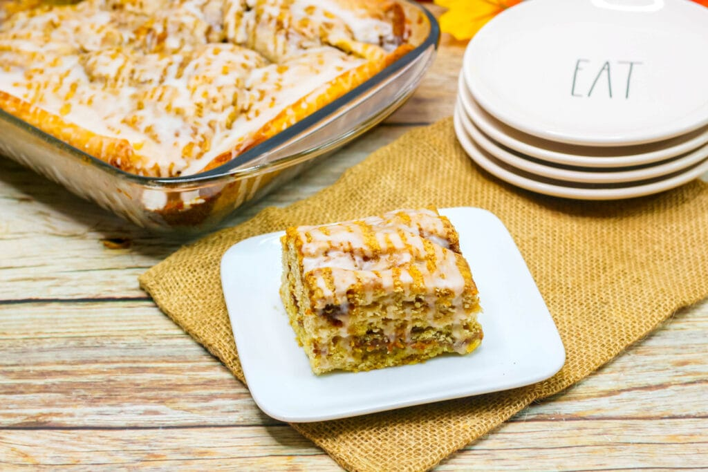 pumpkin cinnamon roll cake next to pan