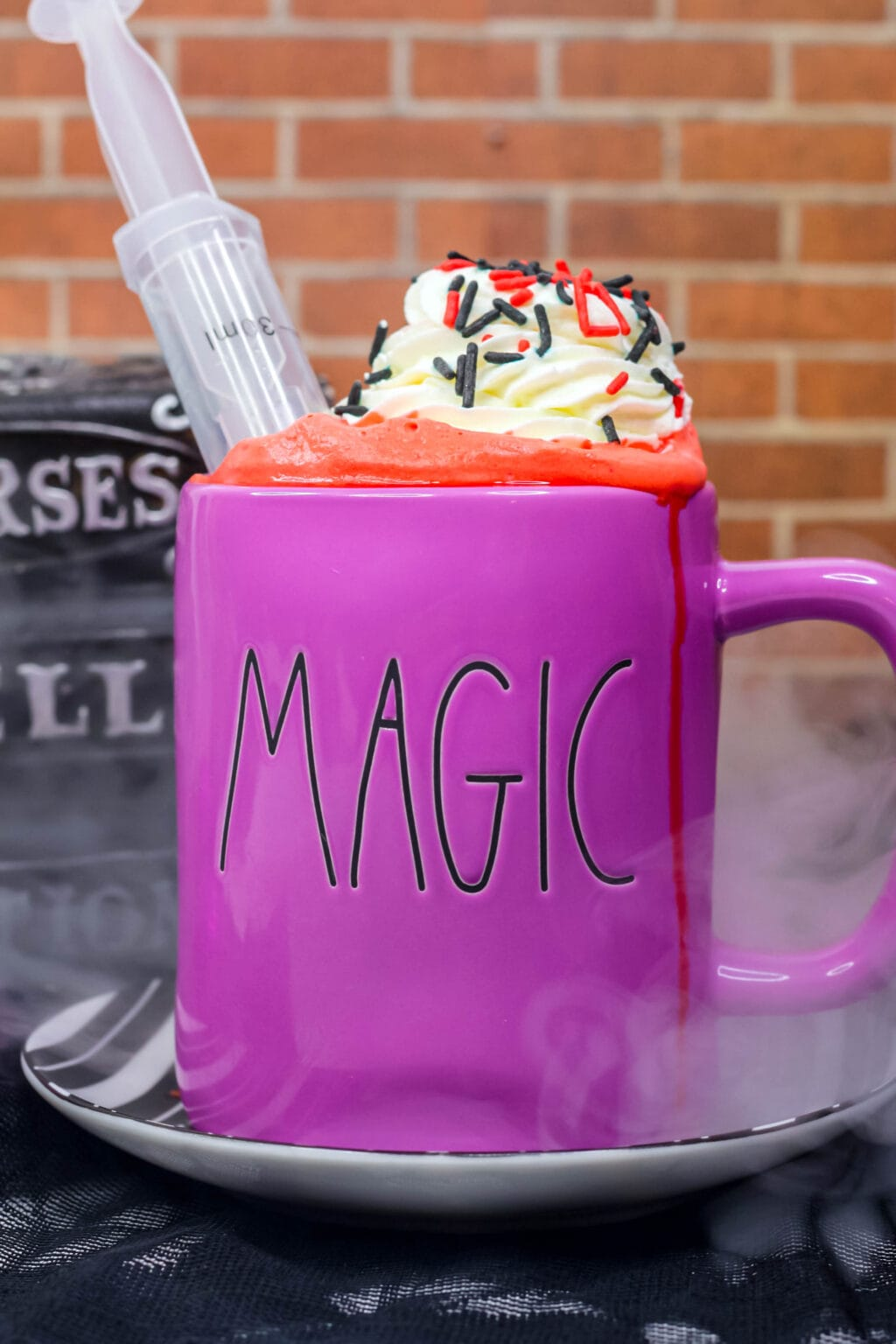 red hot cocoa in a mug with whipped cream and sprinkles on top