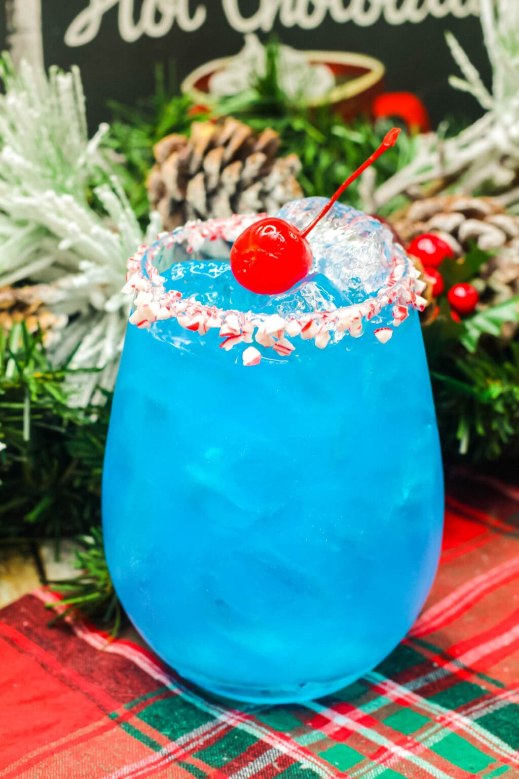 blue cocktail in a glass with peppermint pieces around the rim