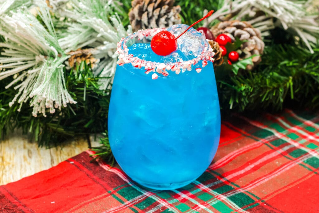 blue cocktail in a glass with red cherry on top