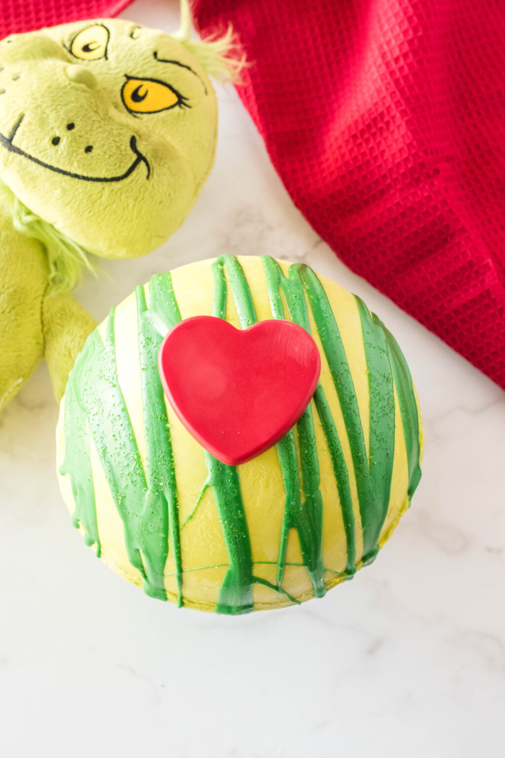 giant grinch hot cocoa bomb on table