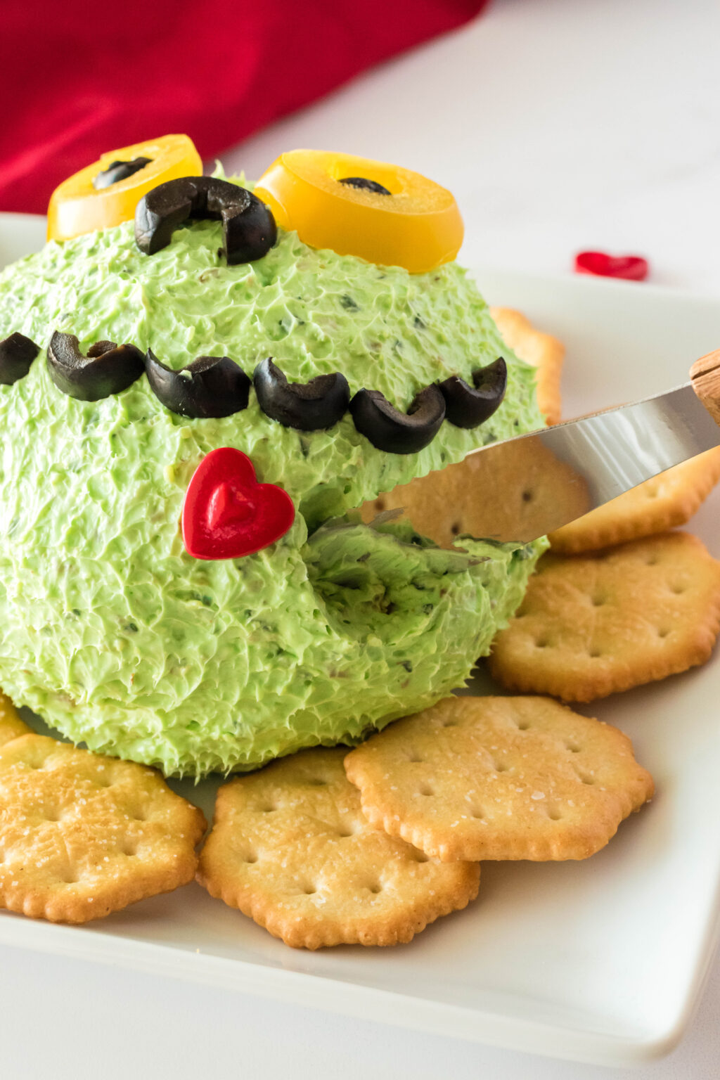 grinch cheese ball being served with knife