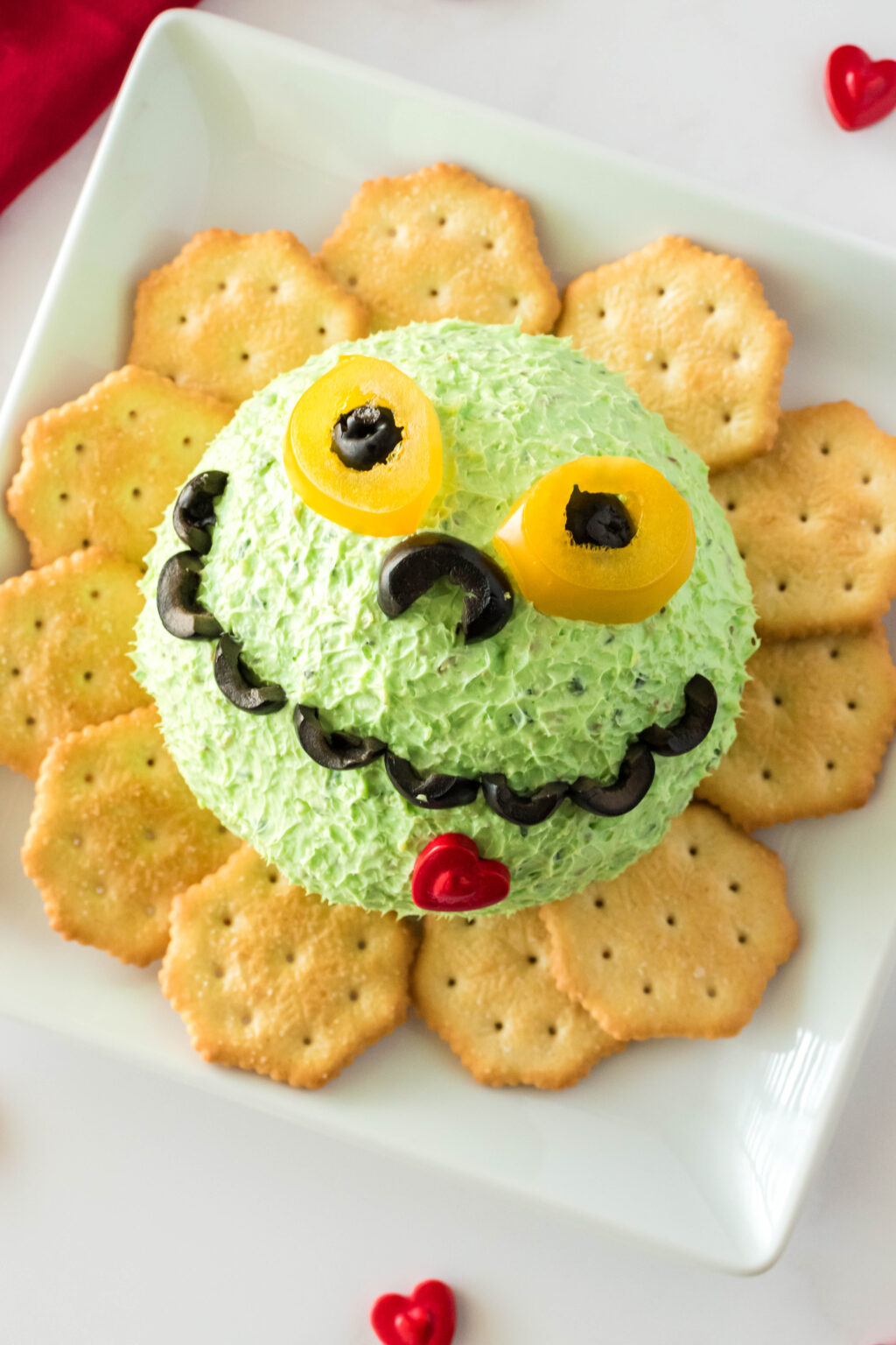 grinch cheese ball on plate with crackers