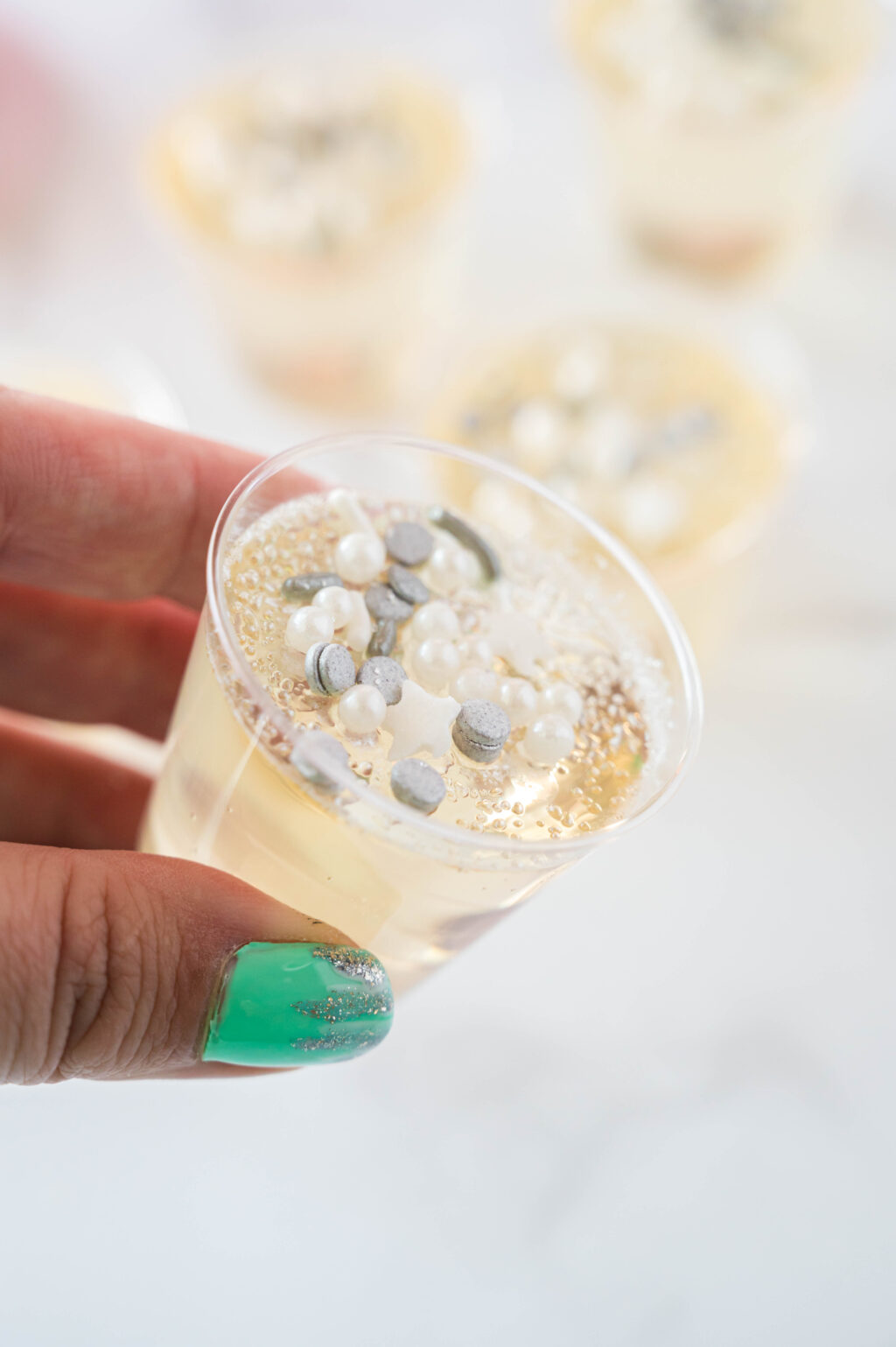 woman holding champagne jello shot