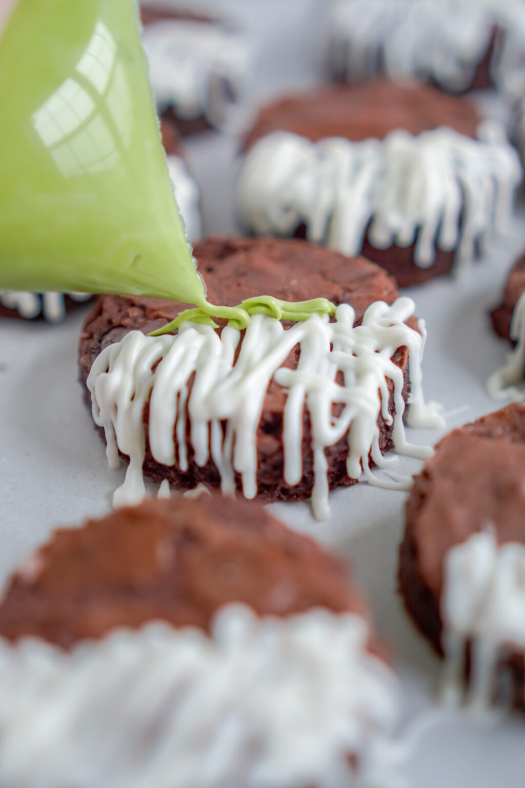 green chocolate being drizzled onto brownie
