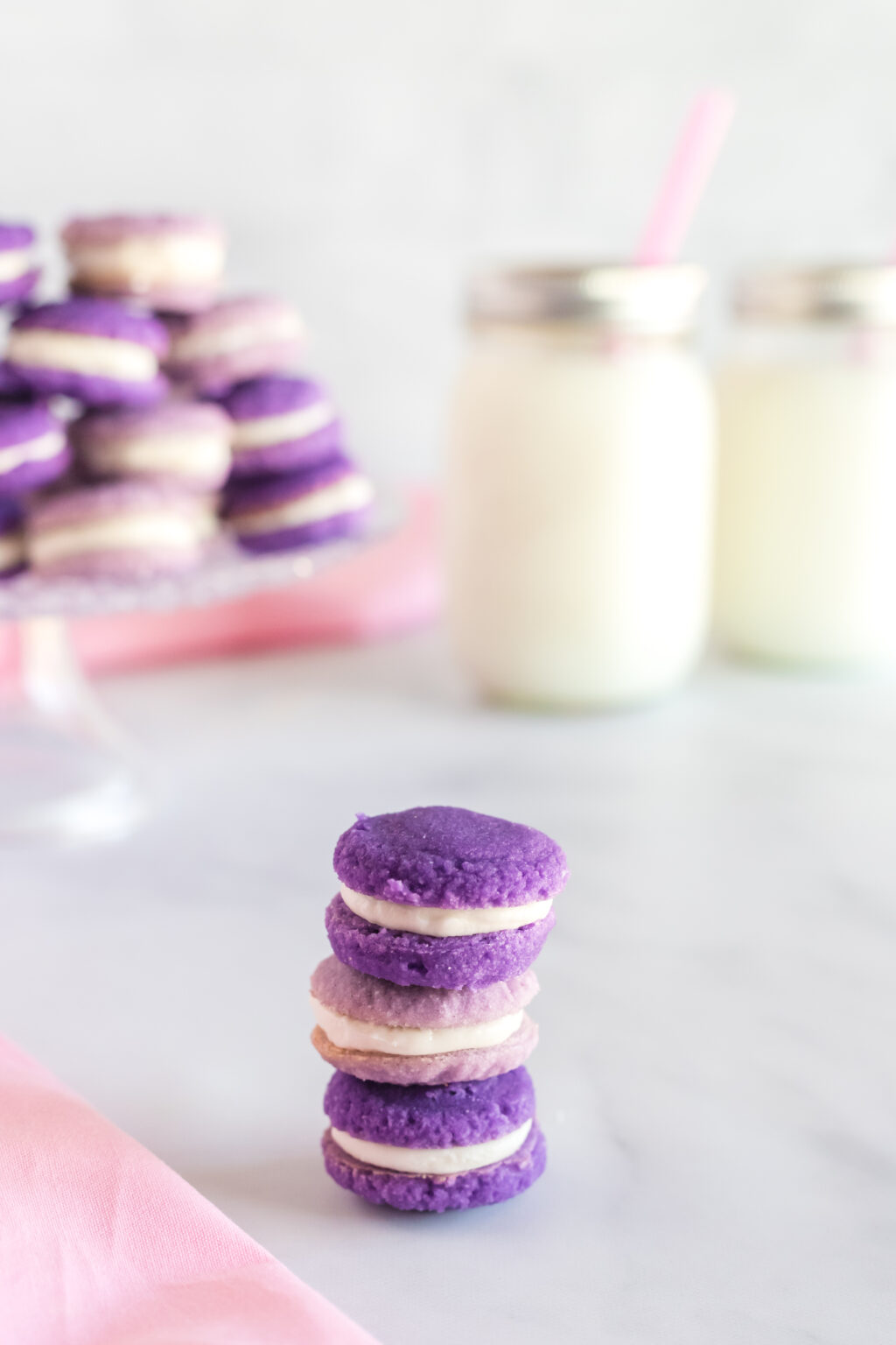 Lavender Macarons stacked on table with milk in background