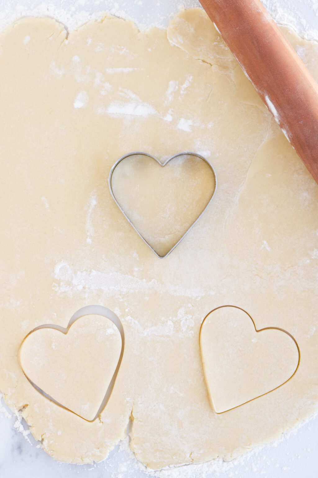 cookie dough being cut into heart shapes