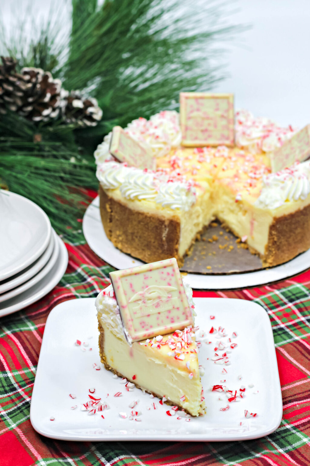 large peppermint cheesecake on a pan beside a slice of white chocolate peppermint cheesecake