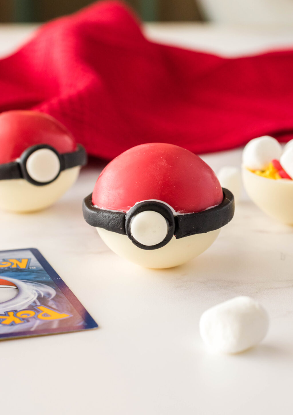 poke ball hot chocolate bomb on table with pokemon cards