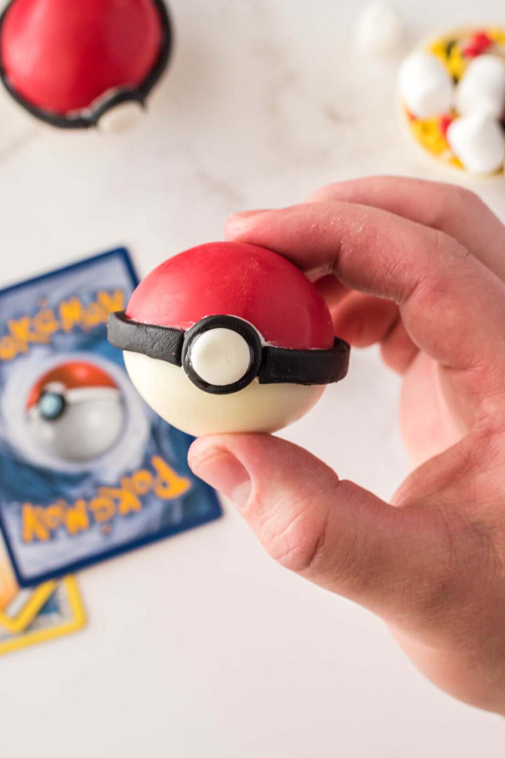 poke ball hot chocolate bomb being held with fingers