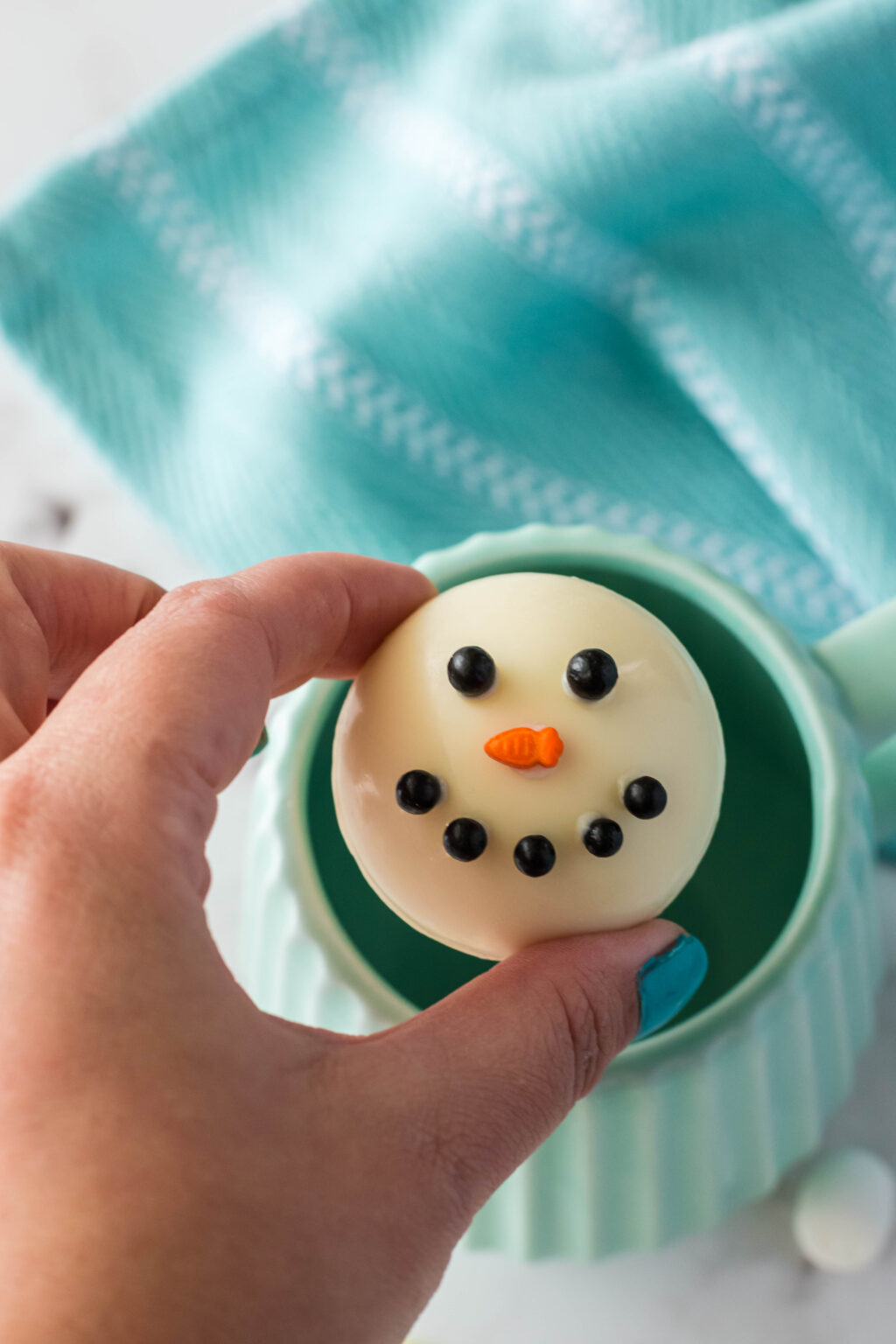 snowman hot chocolate bomb over a mug