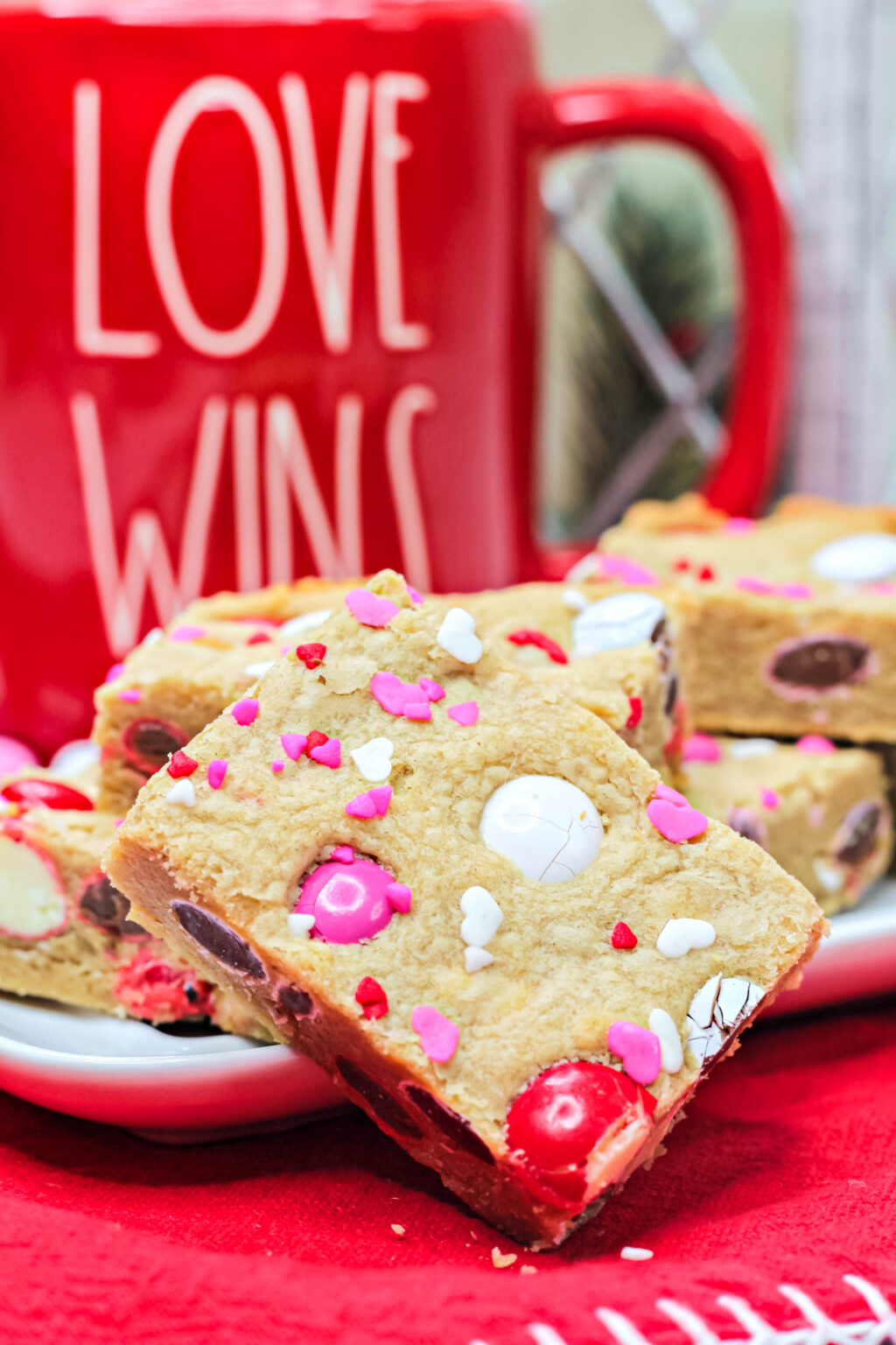square valentine cookie bars with valentine M&Ms and heart sprinkles