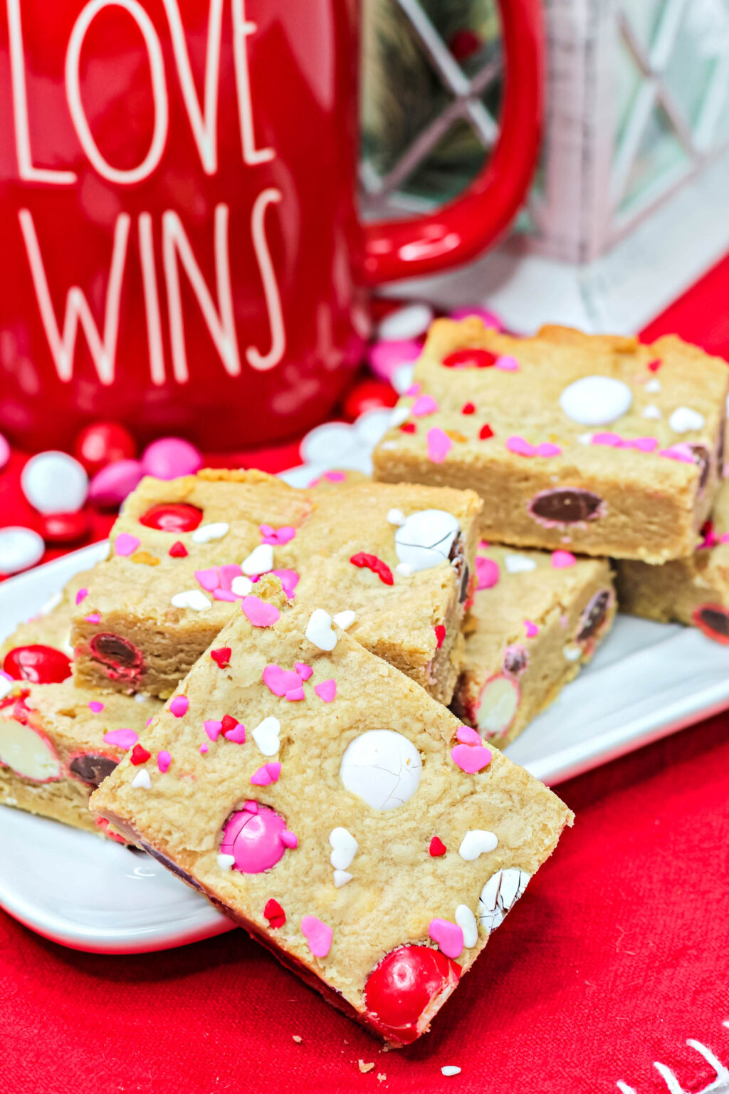 valentine cookie bars with valentine sprinkles and M&Ms cut on a plate
