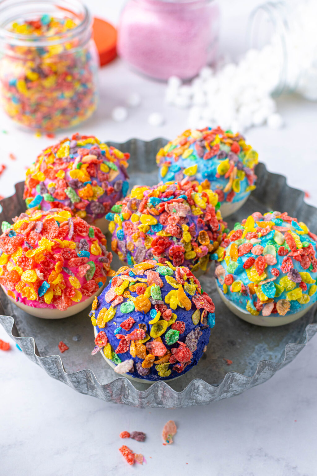 fruity pebbles hot cocoa bombs on a plate