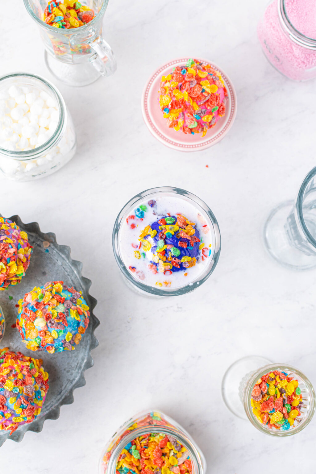 fruity pebble hot cocoa bomb melting in glass of milk