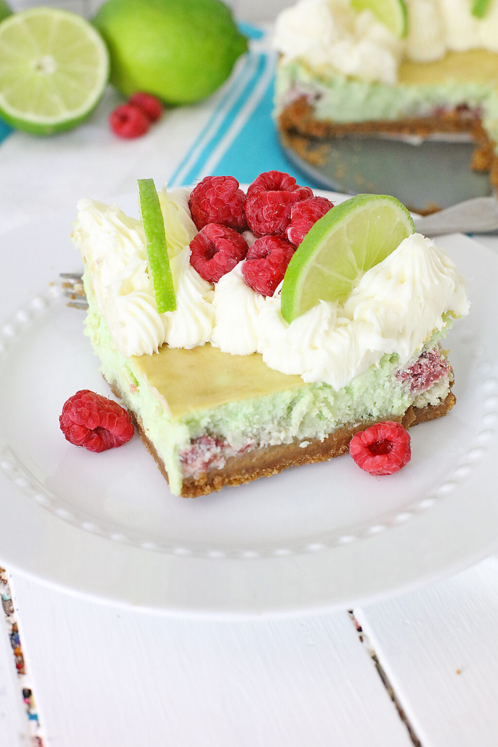 raspberry lime cheesecake slice on a white plate