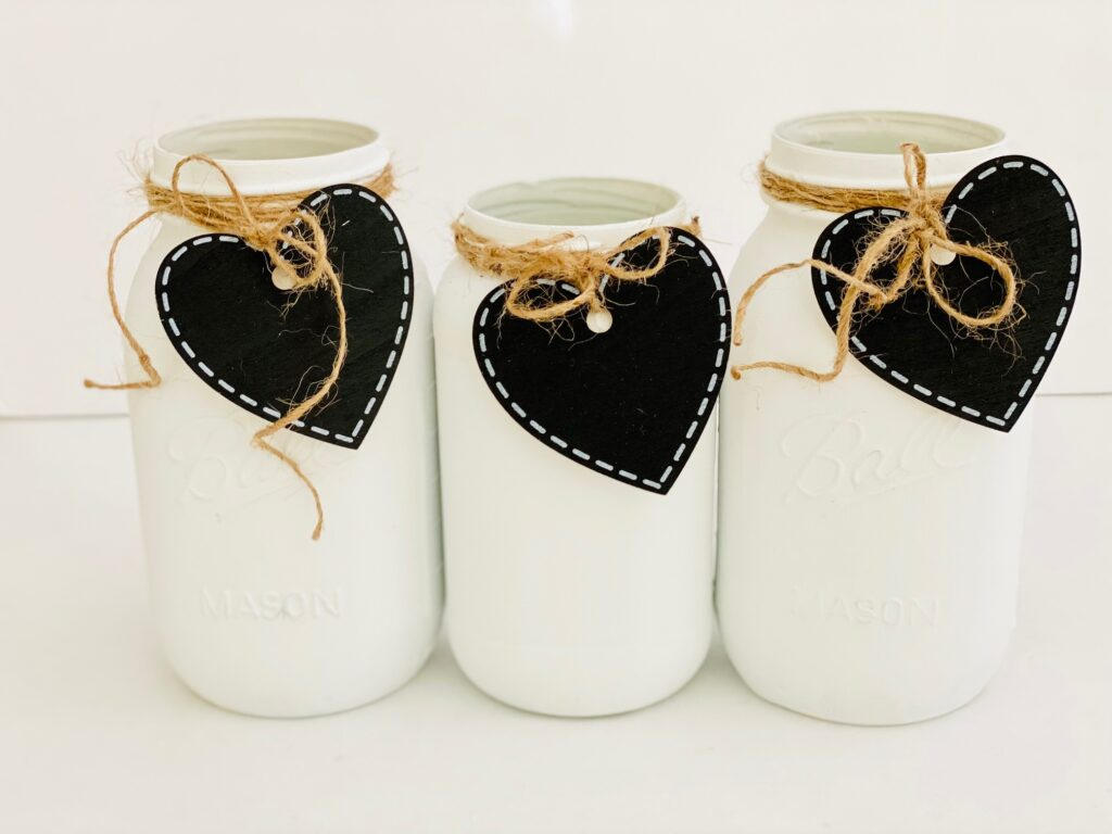 white mason jars with heart tags on them